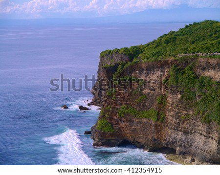 sunlight, blue skies, white clouds and waves splashing along the rugged Big Sur coastline, viewed from jagged cliffs - stock photo