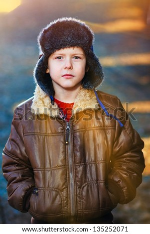 sunlight boy in brown jacket and fur hat on street on blue abstract background - stock photo