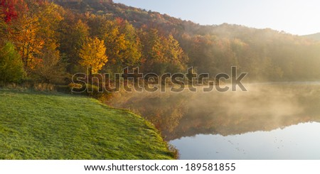 Sunlight burning off the morning fog on Alder Lake on a colorful Autumn day in the Catskills Mountains of New York - stock photo