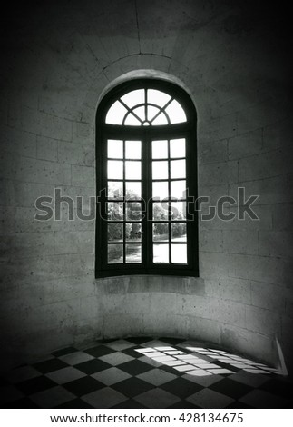 Sunlight coming through the window of an old building. Black and white photo.