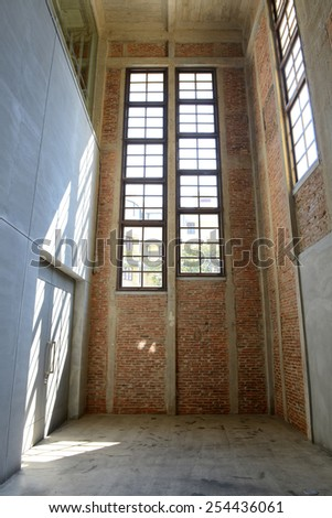 Sunlight from window on the cement walls and floor inside of old building - stock photo