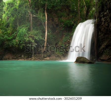 Sunlight in jungle rainforest with scenic waterfall flowing in natural pond - stock photo