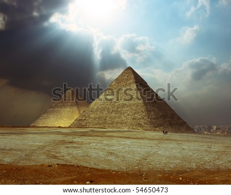Sunlight over grate Giza pyramids. - stock photo