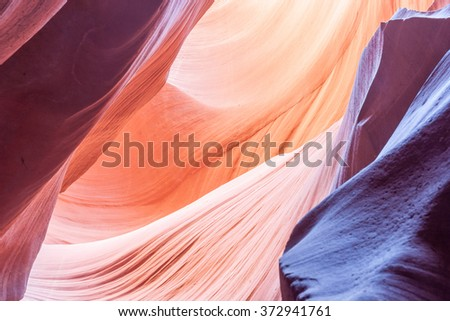 Sunlight plays deep into Lower Antelope Canyon creating the amazing colors purple pink orange and patterns the light reflecting on silica rich limestone surface  Page Arizona USA - stock photo