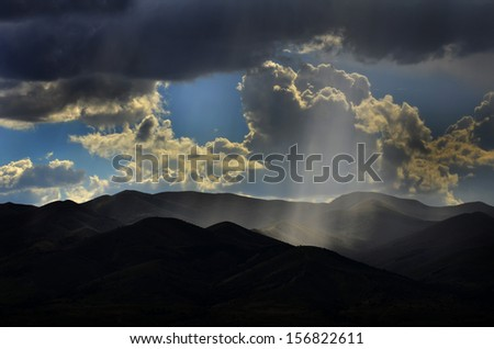 Sunlight rays from clouds falling on dark mountain range - stock photo