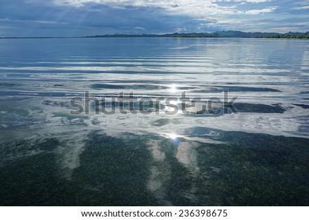Sunlight reflected on calm water surface with cloudy sky and islands at the horizon, Dolphin bay, archipelago of Bocas del Toro, Caribbean sea, Panama - stock photo