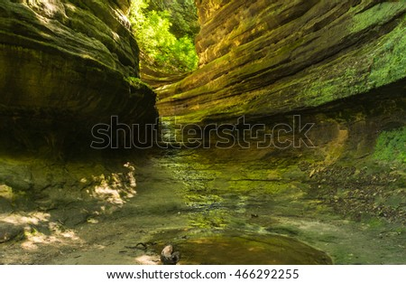 Sunlight shining into Aurora Canyon as water softly flows through the canyon.  Starved Rock State Park, Illinois, USA.