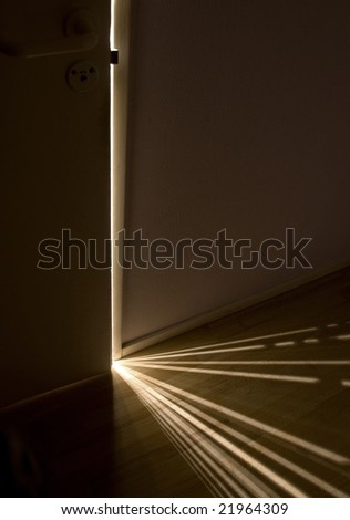 Sunlight shining through a small gap between the door an the wall, creating a pattern on the floor. - stock photo