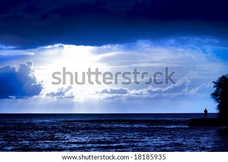 Sunlight through clouds on the dark sea - stock photo