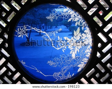 Sunlight through the Chinese blue glass with a bird. - stock photo