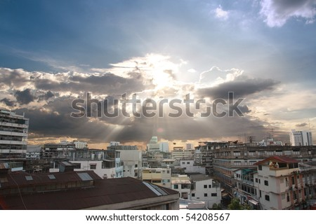 Sunlight through the clouds over the city - stock photo