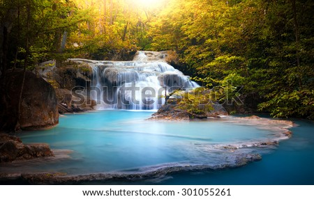 Sunlight through tree leaves lights beautiful waterfall in forest - stock photo