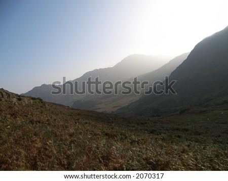 Sunlit mountainside - stock photo