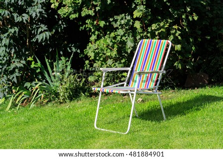 Sunlit rainbow colour striped Deck Chair on lawn