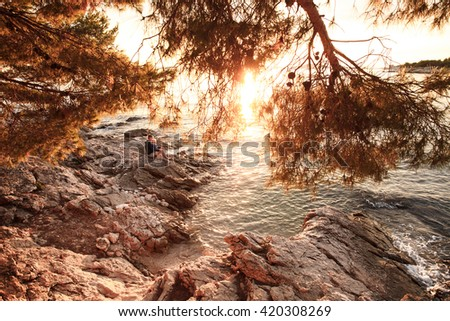 Sunlit rocky beach at sunset with mother and son sitting on shore, cuddling, having fun and enjoying their bonding time together. Family values, travel, tranquility and serenity concept.  - stock photo