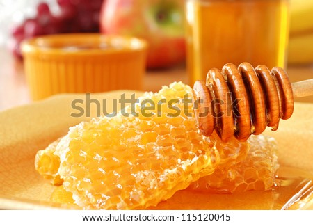 Sunlit still life of golden honeycombs with fresh honey and drizzler.  Jars of honey and fresh fruit in background.  Closeup with shallow dof. - stock photo
