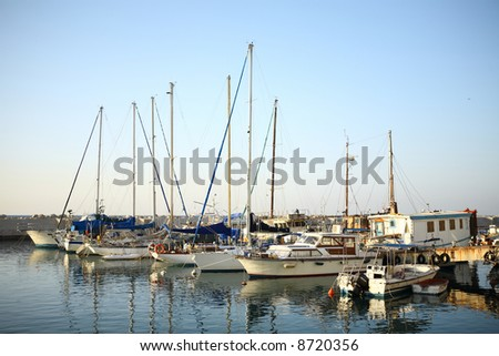 sunlit yachts and boats reflected on water at marina with clean blue sky as background