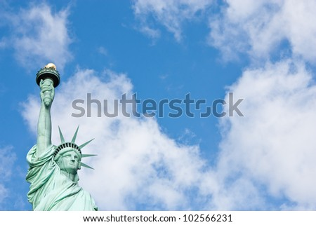Sunnny day, blue sky with clouds: statue of Liberty with copy space - stock photo