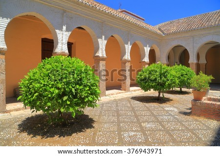 Sunny arches and small trees decorate the Patio of San Salvador church, Granada, Andalusia, Spain