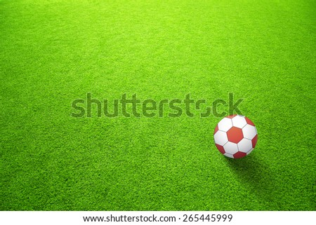 Sunny artificial green grass with red color soccer ball background. Selective focus used.