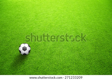 Sunny artificial green grass with soccer ball background. Selective focus used.