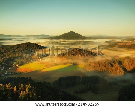 Sunny autumn sunrise in a beautiful mountain of Czech-Saxony Switzerland park. Warm sun rays fight to cold ground mist in valley. - stock photo