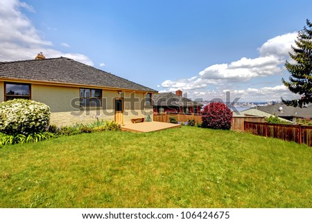 Sunny backyard with green grass and one story home. - stock photo