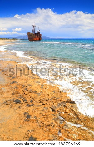 Sunny beach and rusty shipwreck in Gythio, Greece