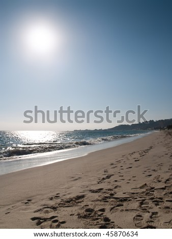 sunny beach shot at malibu beach. sand, ocean, clear sky and bright sun. - stock photo