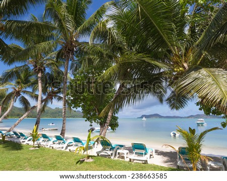 sunny beach with blue sun loungers, coconut trees and boats in the clear sea, Seychelles