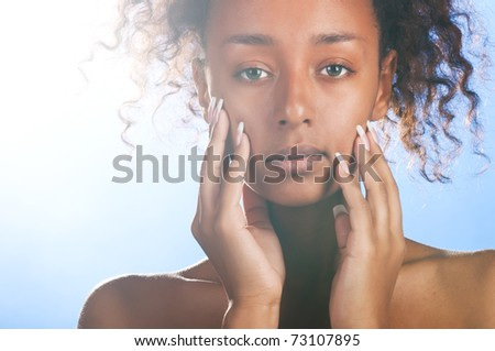 sunny beautiful mulatto woman is looking at camera on sky background - stock photo