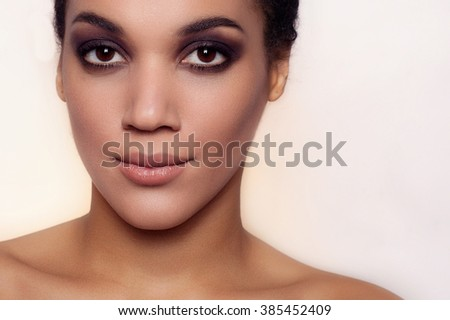 sunny beautiful mulatto woman is looking at camera. studio shot, on a light background