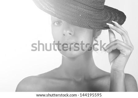 sunny beautiful mulatto woman wearing black straw hat on sky background - stock photo