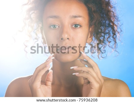 sunny beautiful mulatto woman with is touching her face and looking at camera on sky background - stock photo