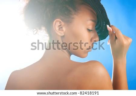sunny beautiful woman wearing black straw hat on sky background - stock photo