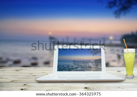 Sunny bright office with a computer on the beach - stock photo
