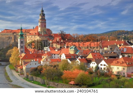 Sunny buildings of a medieval town under cloudy sky in autumn, Cesky Krumlov, Czech Republic - stock photo