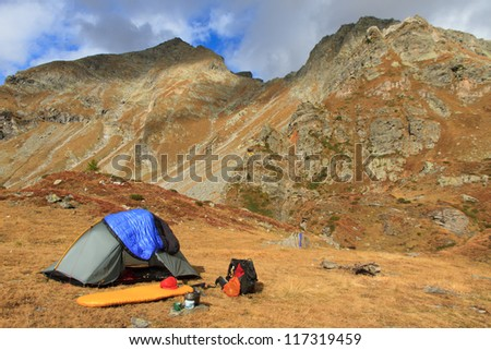 Sunny campsite in the mountains in autumn. - stock photo
