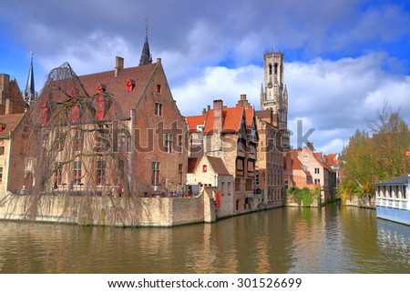 Sunny canal sided by traditional buildings in the old town of Bruges, Belgium