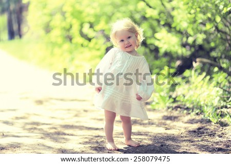 Sunny cute child barefoot in summer day, warm toned colors - stock photo