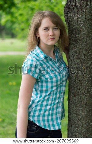 sunny day, a beautiful young girl near a tree.
