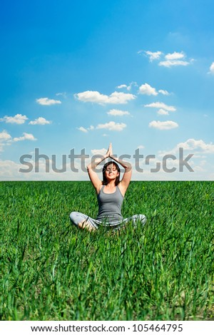 sunny day and woman meditating at the field - stock photo