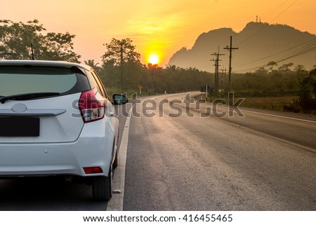 Sunny day at a country, the view on the road level from behind the car - stock photo