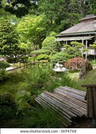 Sunny day in a beautiful Japanese garden with tea house overlooking a pond.