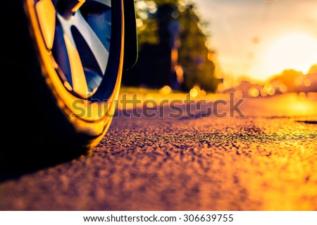 Sunny day in a city, headlights of approaching cars, the view from the road level from the wheel of the car. Image in the orange-purple toning - stock photo