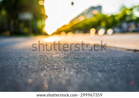 Sunny day in a city, view from the sidewalk level to the stream of cars - stock photo