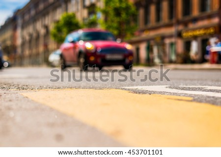 Sunny day in the big city, red car racing on road. View from the pedestrian crossing, focus on the asphalt - stock photo