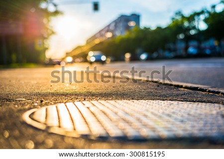 Sunny day in the city, view from the sidewalk level of the hatch at the lights of a car driving up - stock photo