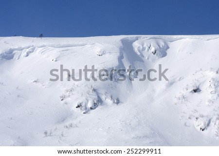 Sunny day on a slope in the Scandinavian mountains. Clean white snow and steep covered cliffs, rocks.  - stock photo