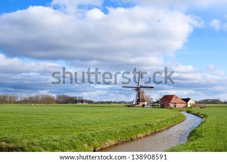 sunny day on Dutch farmland with windmill, Holland - stock photo